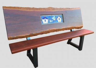 Bench with glass panel of birdhouses in a natural edge backrest